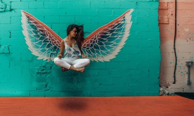 woman taking picture beside wings decor 1328527