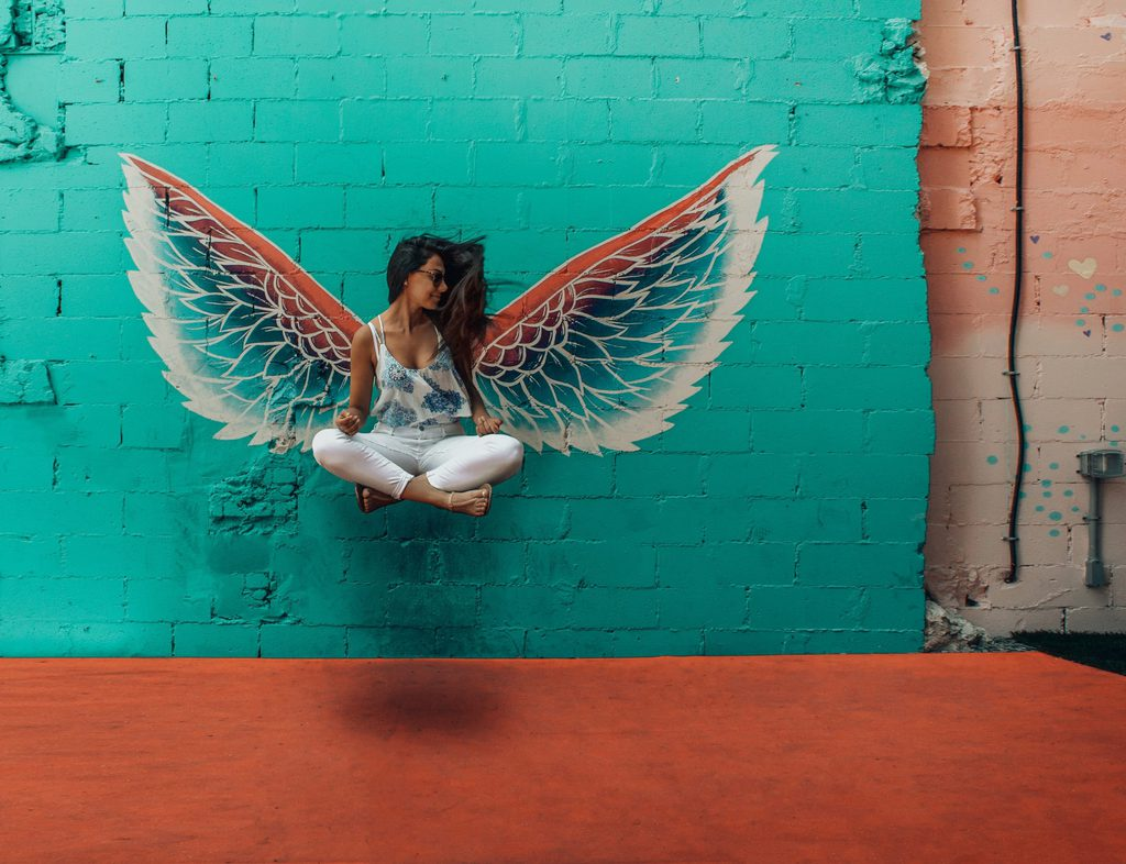 woman taking picture beside wings decor 1328527 scaled