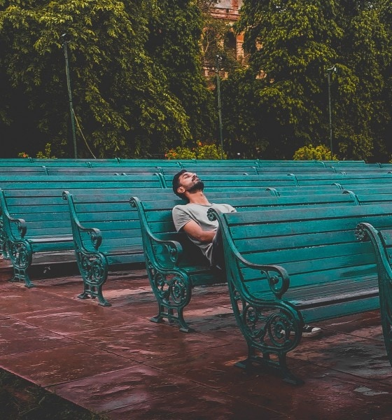 man sitting and closing eyes on teal bench 1076999