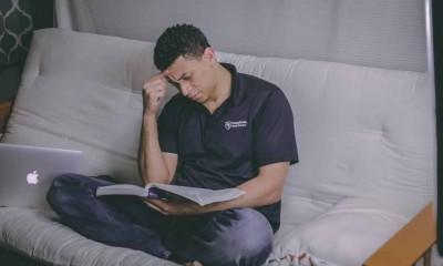 man sitting on sofa reading book 1467564