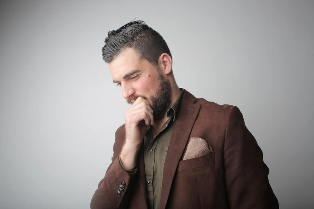 pensive man in brown coat holding his chin 3785078
