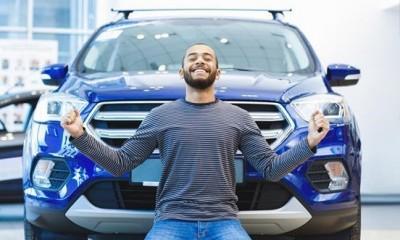 jeune homme barbu levant les bras devant voiture bleue