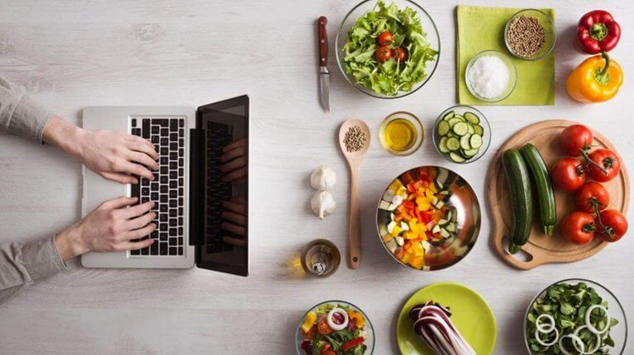 Une personne avec un ordinateur et des aliments